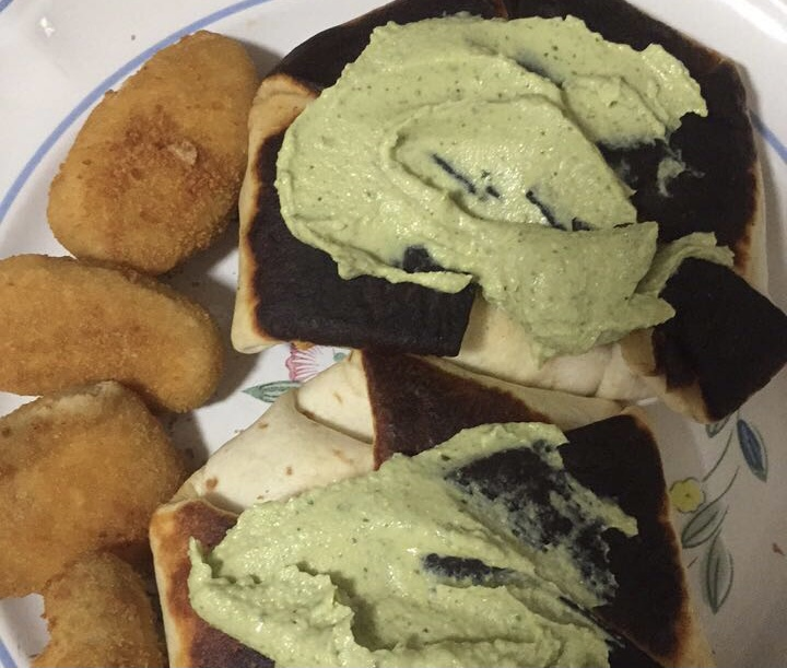 Toasted tortilla with hummus on top and jalepeno poppers on the side